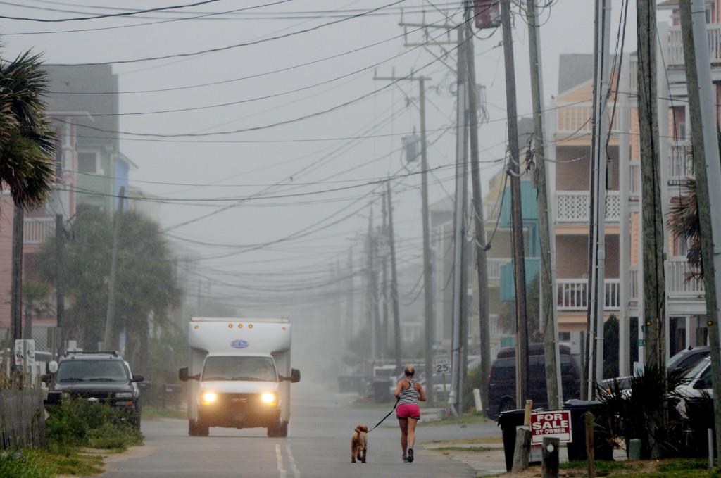 Clouds and rain move in as beachgoers leave Freeman Park at Carolina Beach, N.C. Thursday,  The Associated Press