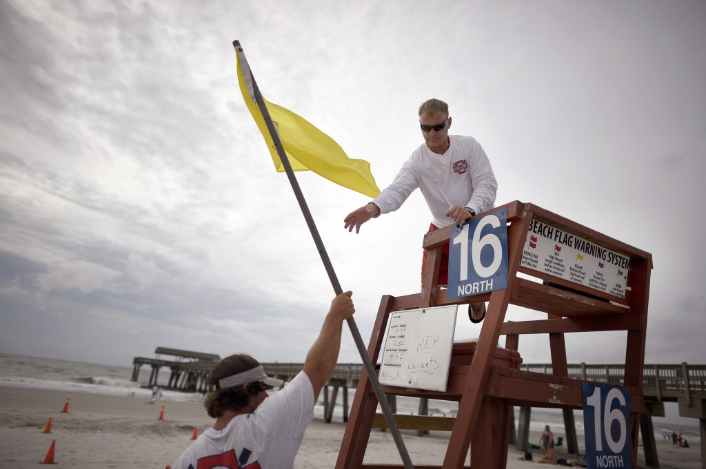 Todd Horne, right, a Tybee Island Ocean Rescue lifeguard, and Mark Eichenlaub hang a yellow flag that warns swimmers of strong rip currents after Hurricane Arthur bypassed the Georgia coast as predicted,  The Associated Press