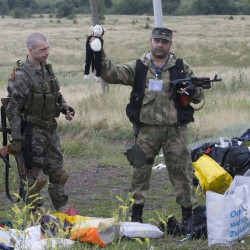 A pro-Russian fighter holds up a toy found among the debris at the crash site of a Malaysia Airlines jet near the village of Hrabove, eastern Ukraine, on Friday.