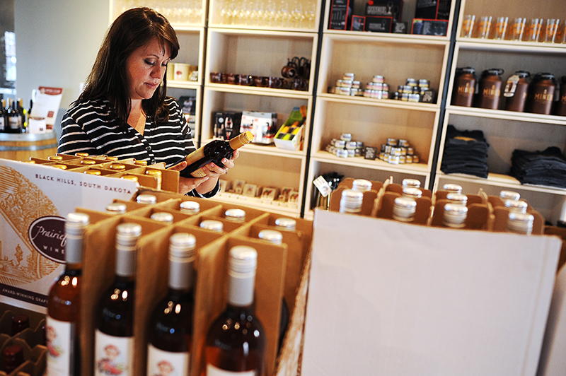 Susan Edwards, of Westborough, Mass., browses the wine selection on Monday, July 7, 2014, at Prairie Berry East Bank in downtown Sioux Falls, S.D. The Associated Press