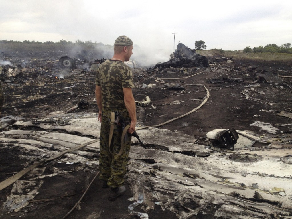 An armed pro-Russian separatist stands at a site of a Malaysia Airlines Boeing 777 plane crash in the settlement of Grabovo in eastern Ukraine on Thursday.