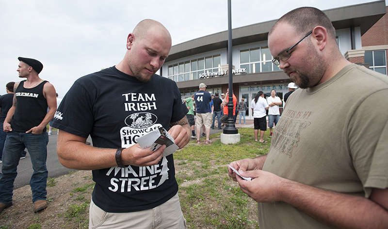 UFC fans Stephen Erland, left, of Surry and David Rey of Ellsworth check their tickets before the doors open  Saturday for the Ultimate Fighting Championship fight night. Kevin Bennett/Special to the Telegram