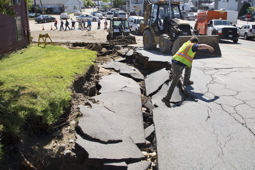 Utility workers surveyed and dug out a hole in front of Rufus Deering Lumber on Commercial Street Thursday, a day after heavy rains and flash flooding damages streets in Portland.