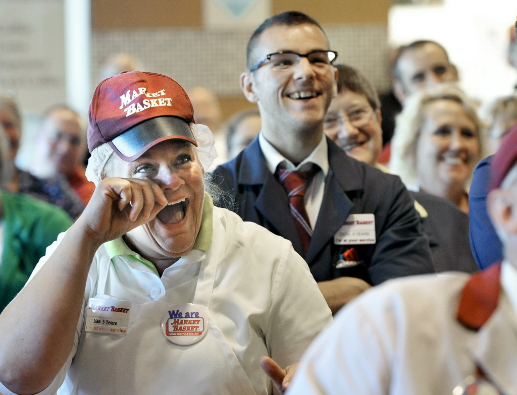 Lisa Lemieux of Salem, N.H., wipes away tears as she is joined by employees watching Arthur T. Demoulas speak during a news conference on a television at the Market Basket in Biddeford on Thursday.