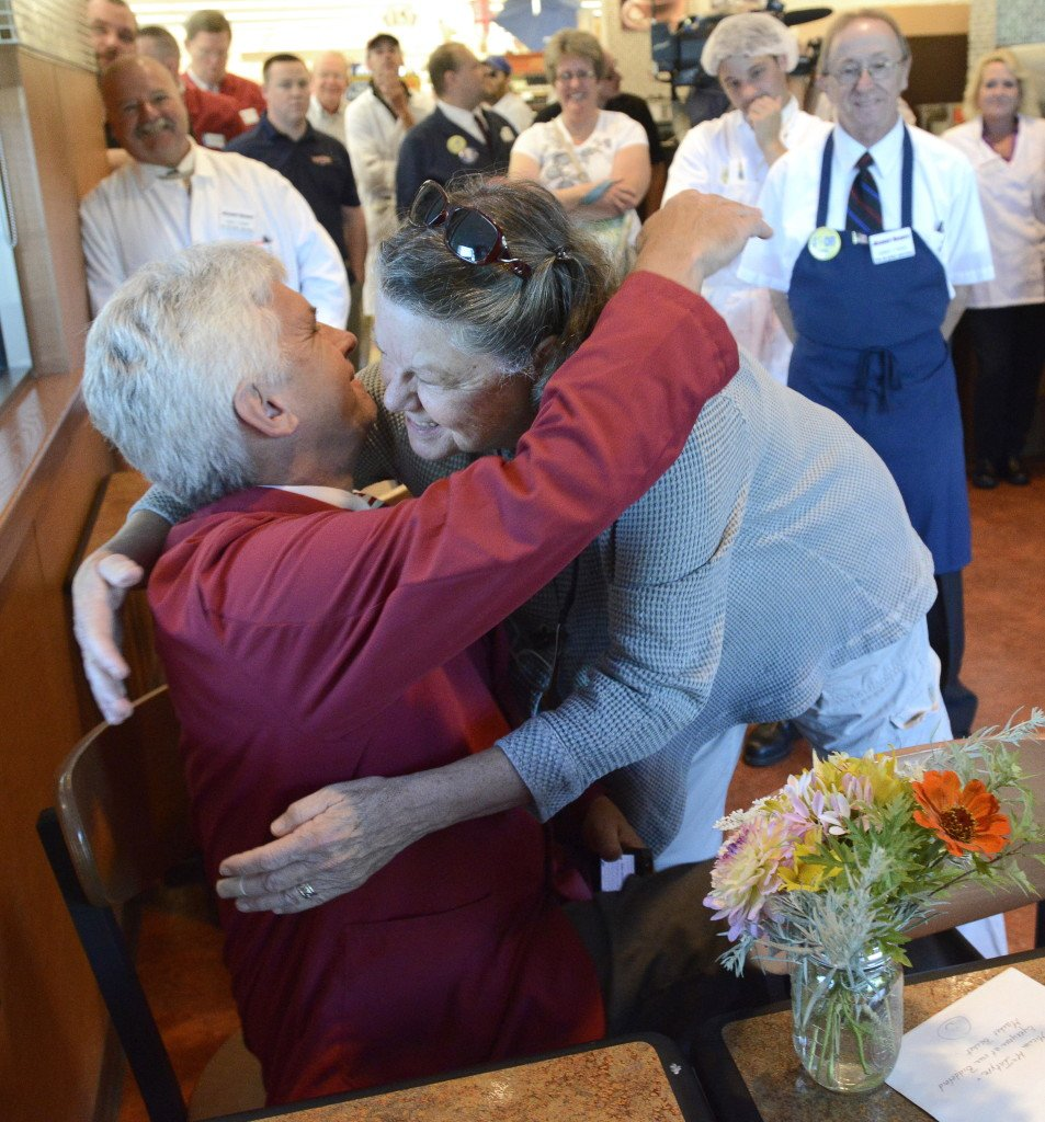 Customer Katherine Mount of Lyman hugs store manager Micum McIntire after giving him flowers as workers and customers celebrate a buyout deal that allows them to get back to work at the Market Basket in Biddeford on Thursday.