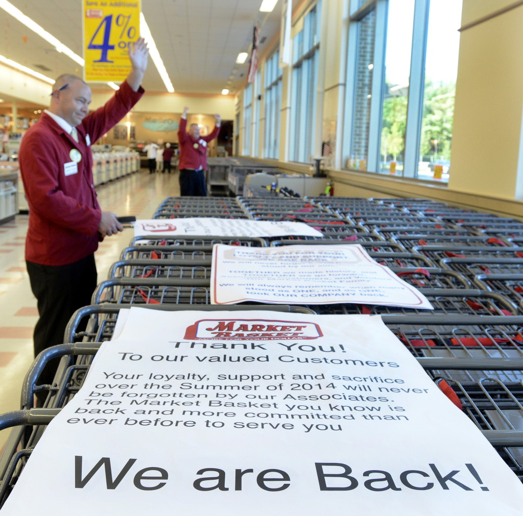 Employees Danny Lassiter and Mike Menard wave to customers outside as workers celebrate the new ownership and getting back to work at the Market Basket in Biddeford on Thursday.