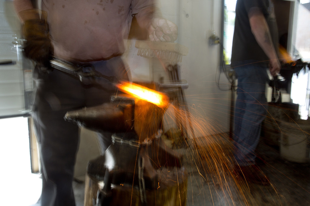 Sparks fly off a hot piece of iron being brushed by Tom Johnson of Kittery Point during a blacksmithing class.