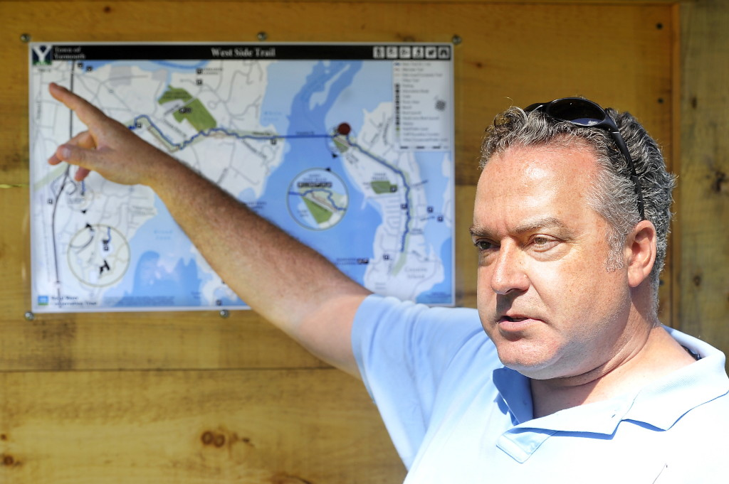 Royal River Land Trust Executive Director Alan Stearns shows the new map of the West Side Trail placed in the new kiosk on Cousins Island and explains the details of the trail system's present and future developments.