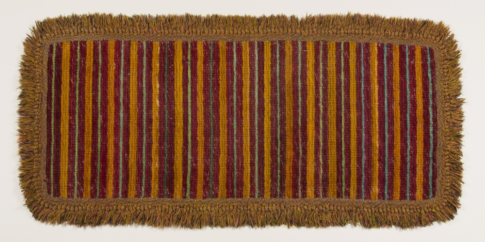 """A woven plush rag rug with """"peacock fringe"""" border, 1890, made by Sister Ada S. Cummings of the Sabbathday Lake Shaker community. A Shaker woven plush rag rug from 1890."""