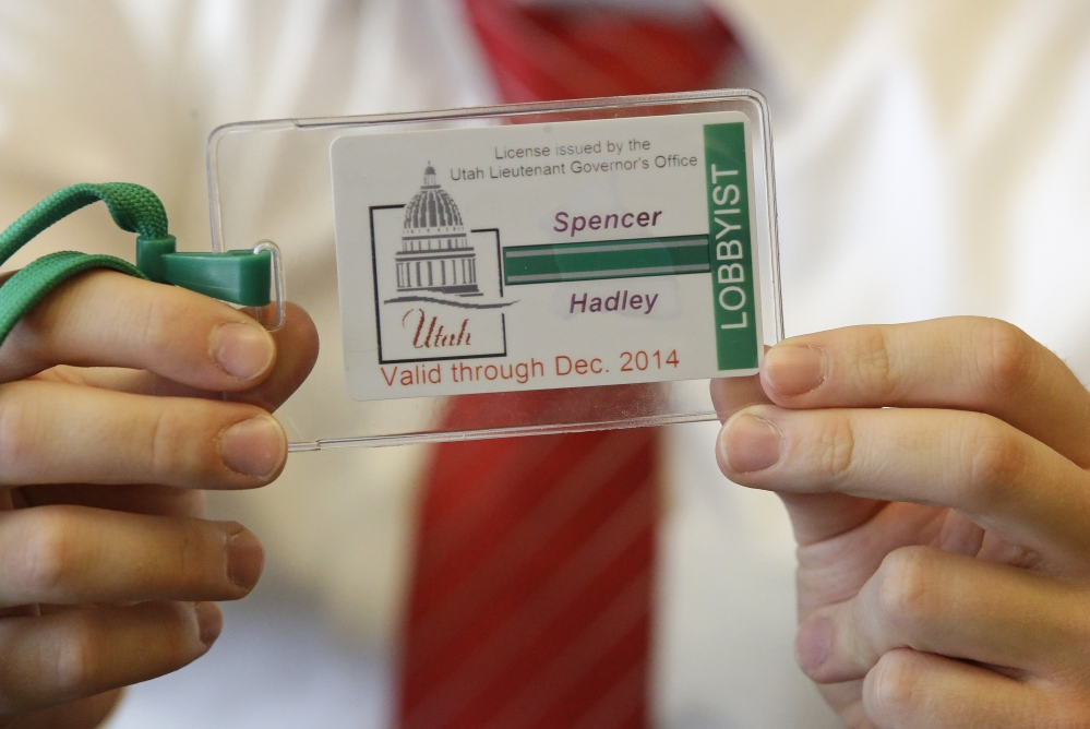 A staff member at the Utah lieutenant governor's office holds a sample badge lobbyists are required to wear as of Friday at the Utah State Capitol in Salt Lake City.