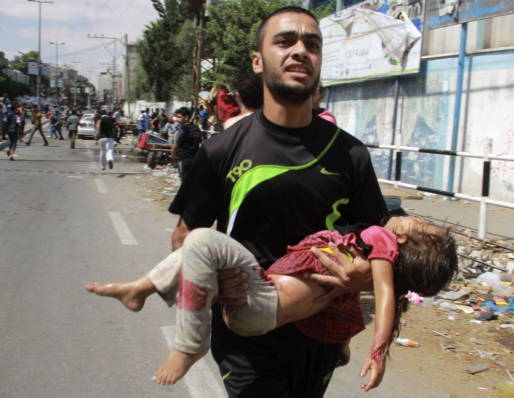 A Palestinian man carries a child killed in an apparent Israeli airstrike Sunday in the southern Gaza Strip near a U.N.-run school that was being used to provide shelter for about 3,000 people.