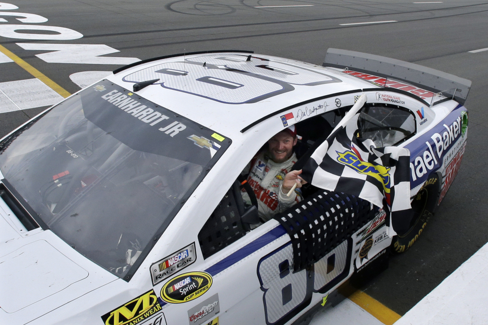 Dale Earnhardt Jr. (88) holds the checkered flag after winning the NASCAR Sprint Cup Series auto race at Pocono Raceway, Sunday, in Long Pond, Pa.
