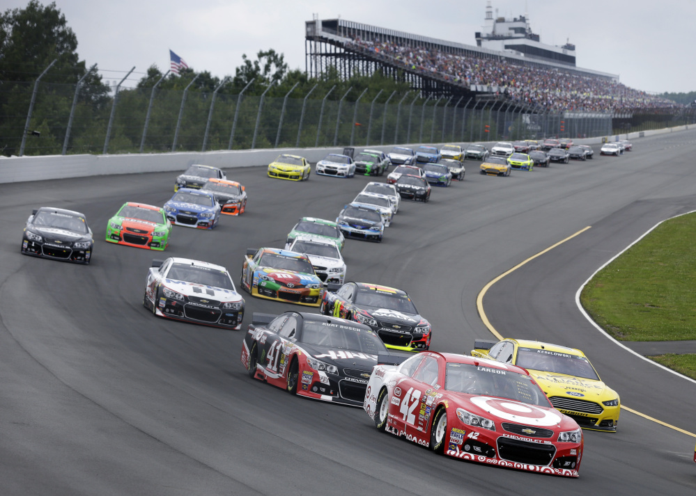 Kyle Larson (42) leads a pack of cars at the start of the NASCAR Sprint Cup Series auto race at Pocono Raceway, Sunday, in Long Pond, Pa.