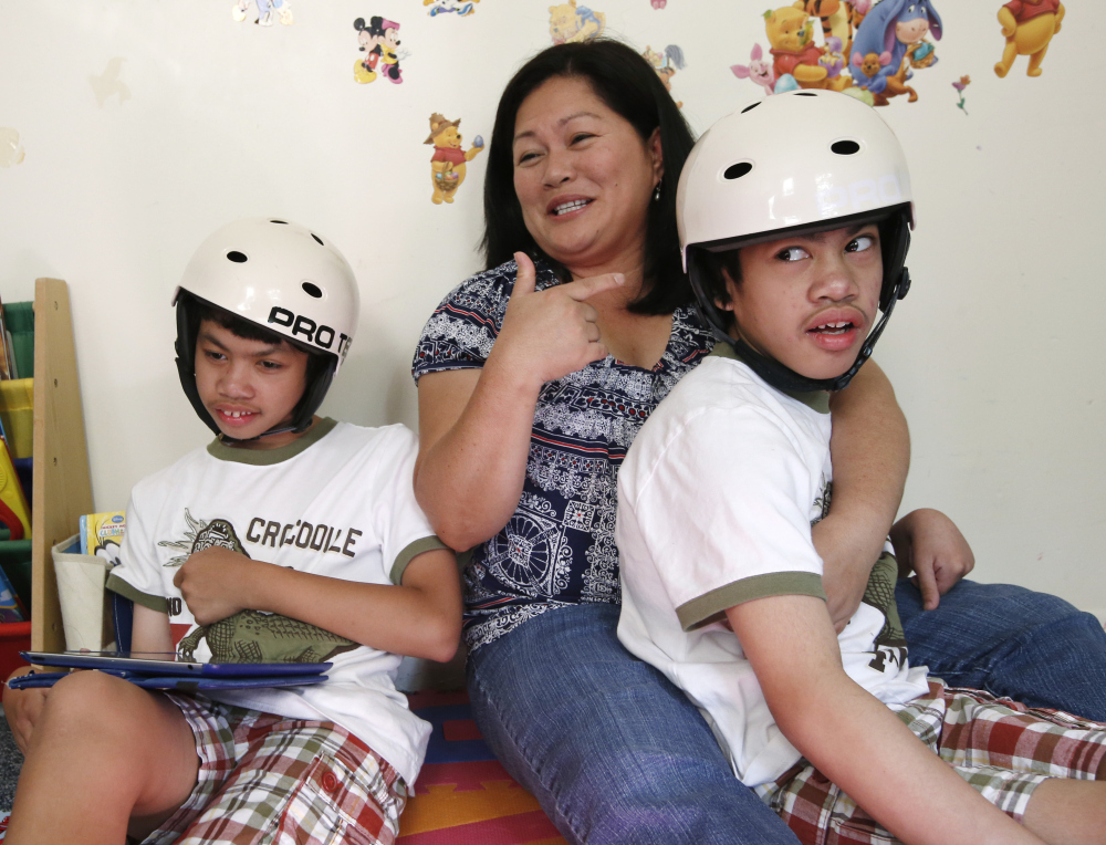Arlene Aguirre, center, sits with her 12-year-old twin sons Carl, left, and Clarence in Scarsdale, N.Y., on Thursday. On Monday, Montefiore Hospital and the family will celebrate the 10th anniversary of the surgery that separated the boys who were born conjoined.