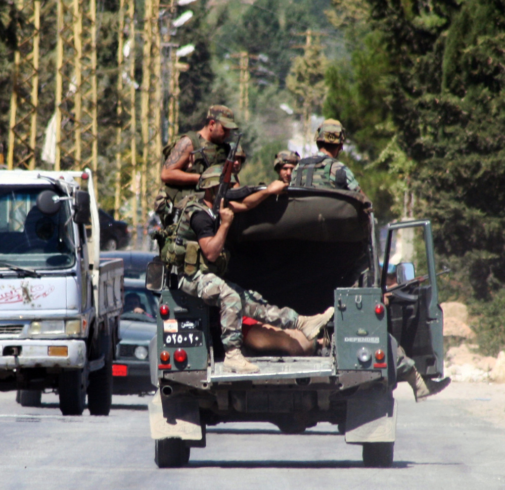 Lebanese soldiers ride in the back of an army vehicle with detained suspected militants in the Lebanese town of Arsal near the Syrian border in eastern Lebanon on Sunday.