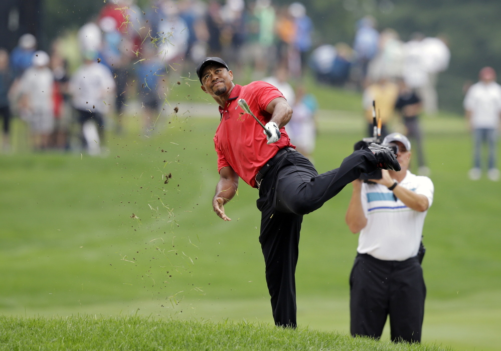 Tiger Woods makes an awkward follow through after hitting from the lip of a fairway bunker on the second hole during the final round of the Bridgestone Invitational golf tournament Sunday,  at Firestone Country Club in Akron, Ohio. The Associated Press