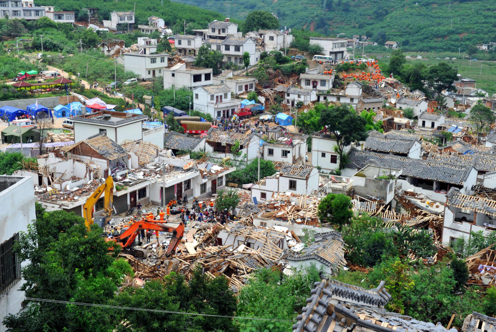 Collapsed houses are seen in Ludian County of Zhaotong City in southwest China's Yunnan Province, Monday, Aug. 4, 2014, following Sunday's strong earthquake.  Rescuers dug through shattered homes Monday looking for survivors of the strong earthquake in southern China's Yunnan province that killed hundreds and injured more than a thousand people.