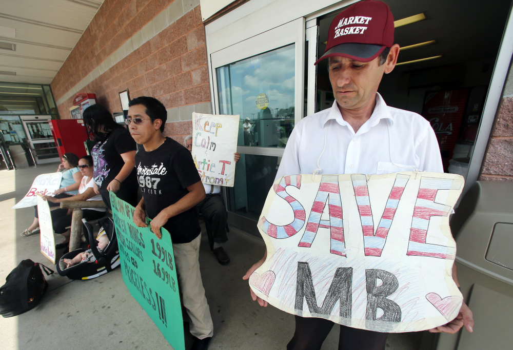 Ardian Zoto, right, an employee of Market Basket for six years, holds a sign outside the supermarket in Danvers, Mass., on Monday.