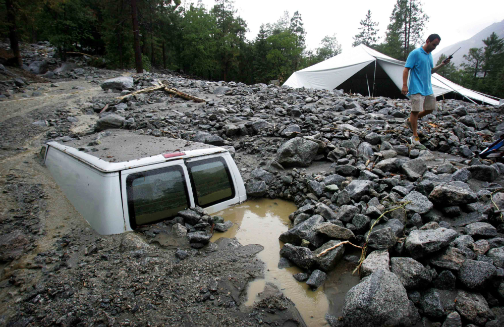 An official of Forest Home Christian Conference Center in Forest Falls, Calif., inspects damage on the property caused by Sunday's thunderstorms.