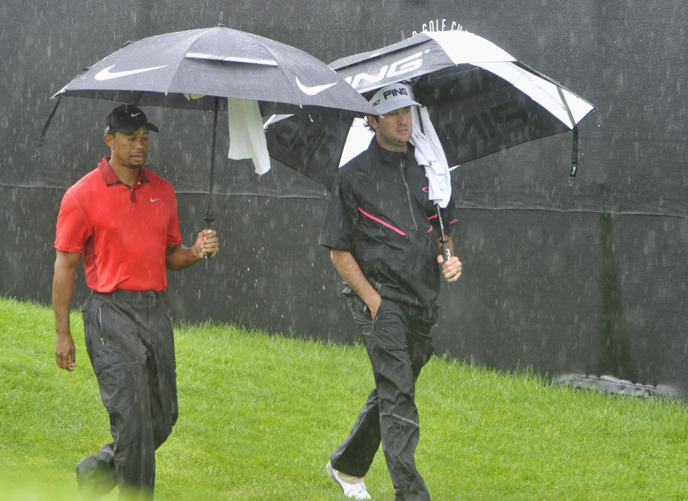 Tiger Woods, left, and Bubba Watson, walk off the course because of a rain delay at the first hole of the final round of the Bridgestone Invitational golf tournament, Sunday, in Akron, Ohio.