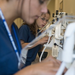 Emma Cost and Courtney Ouellette carefully trim teeth molds Monday at the University of New England's dentist camp for high school students.