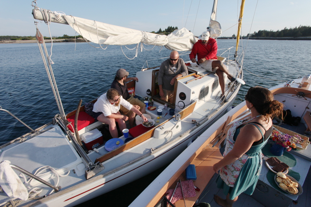 Reilly Harvey, right, speaks with, from left, Sarah Anderson, Josh Anderson, Joe Godfrey, and Dale Young, after cooking them lobster and steamers on her boat in the harbor between Dix Island and High Island.