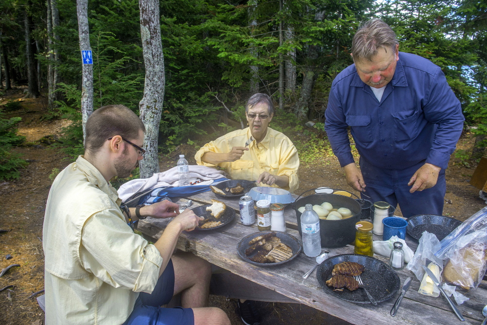Maine guide Lance Wheaton prepares a traditional shore lunch for his clients, Phil Kadzielawski and his grandmother Mary Anne Kadzielawski.