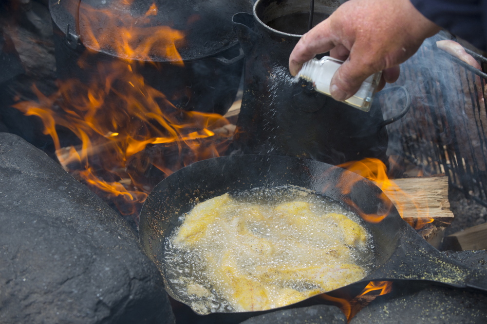 Guide Lance Wheaton adds a dash of salt to fish filets frying over a wood fire.