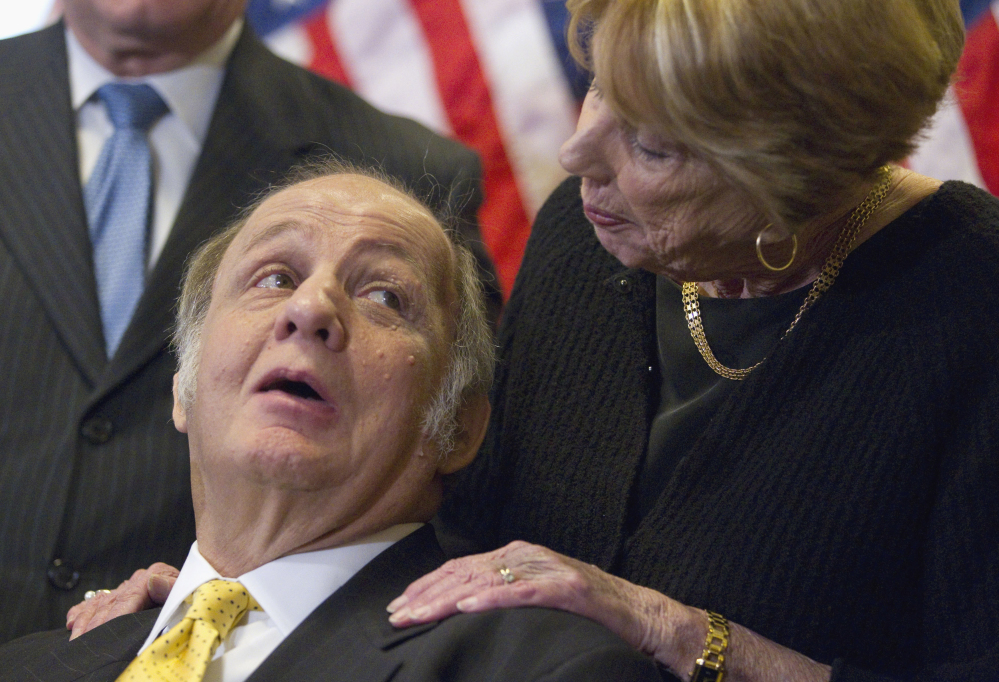 Former White House press secretary James Brady, left, who was left paralyzed in the Reagan assassination attempt, looks at his wife Sarah Brady during a 2011 news conference on Capitol Hill in Washington marking the 30th anniversary of the shooting.