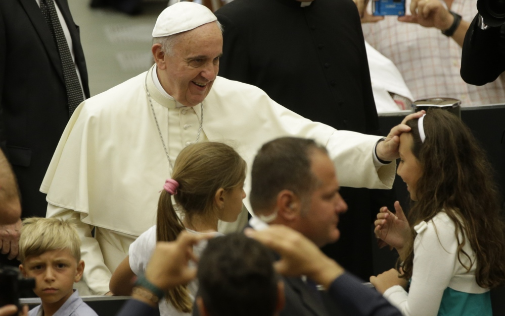 Pope Francis blesses a child at the Vatican on Wednesday. He will fly over China en route to Korea on Aug. 13.