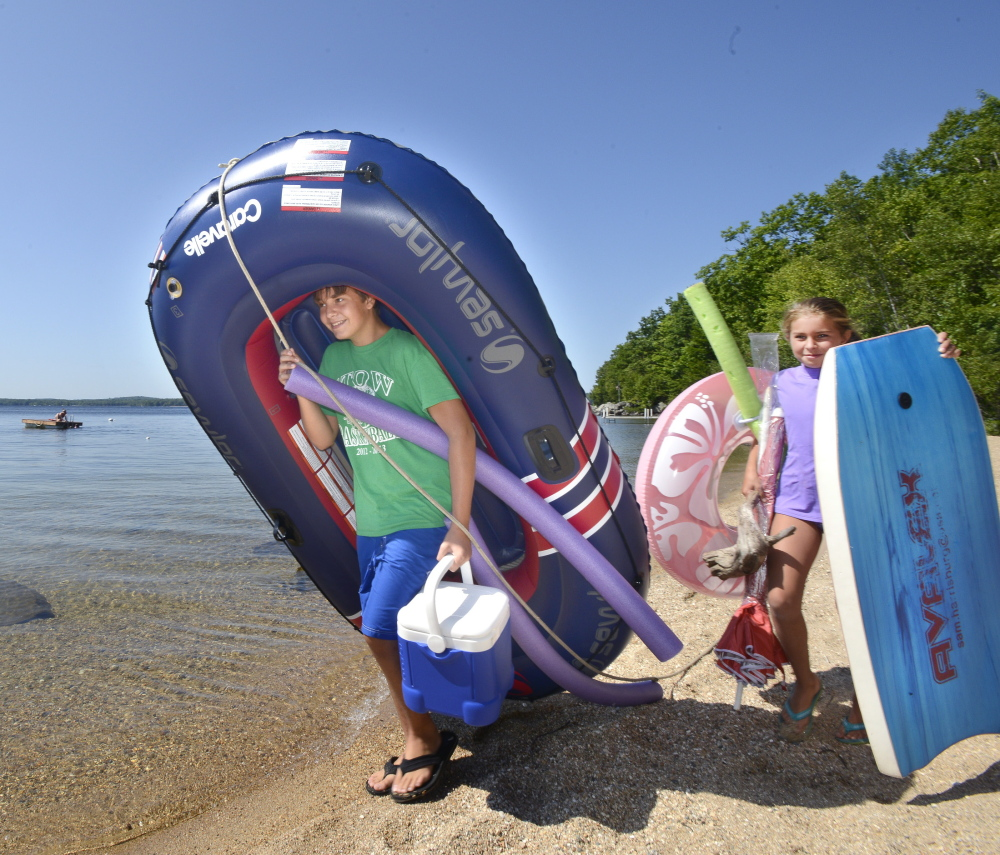 John Donovan, 12, and his 8-year-old sister Emma, both of Stow, Massachusetts, carry their rafts to Long Beach on Frye Island.