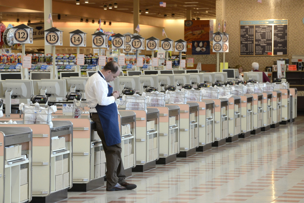 Part-time employee Isaac Ward waits for customers at the checkout counters at the Market Basket in Biddeford last week. The store is out of perishable items because most deliveries have stopped during an ongoing dispute between the company's owners.