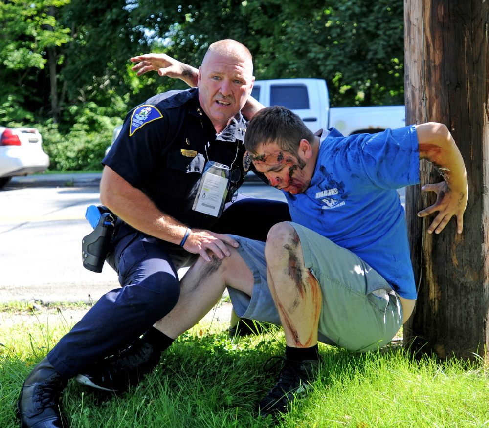 Farmington Police Chief Jack Peck helps a man portraying a victim of a car bombing during a Homeland Security training exercise at the University of Maine at Farmington.