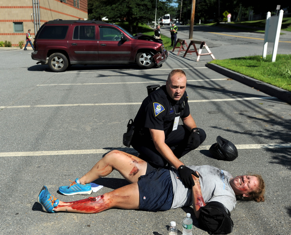Darin Gilbert, Farmington police officer, tends to  person portraying a car bombing victim in a parking lot at the University of Maine at Farmington during a large-scale Homeland Security training exercise.