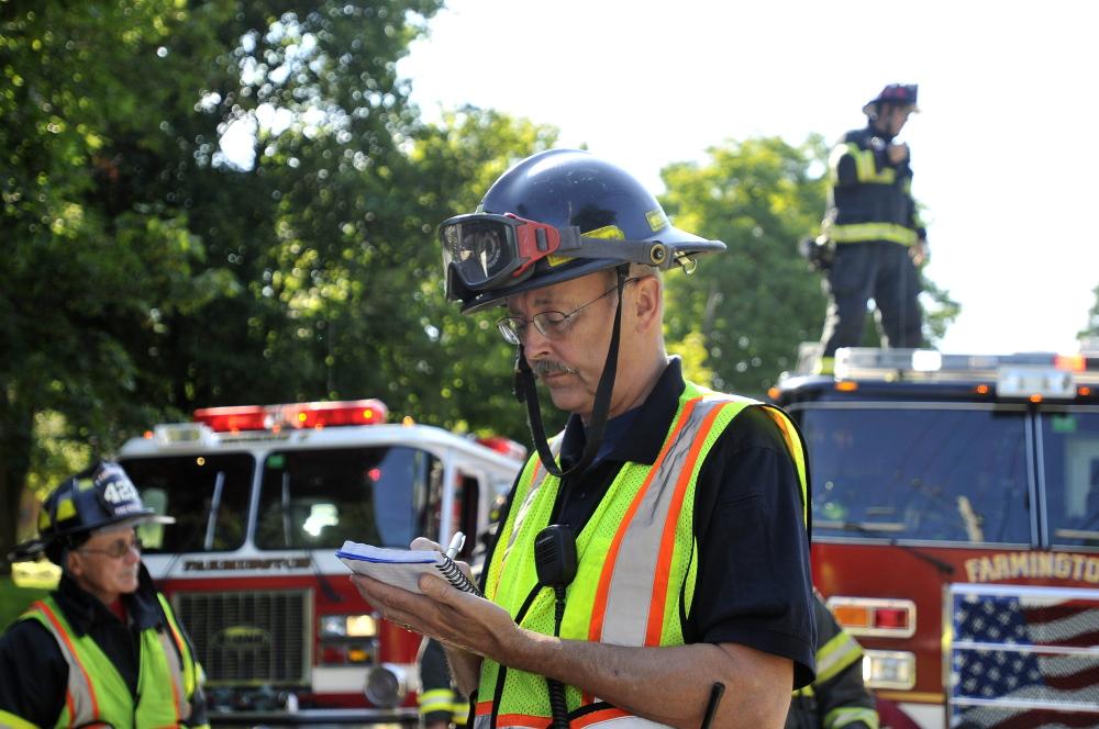 Farmington firefighter, Steve Bunker, takes notes during simulated emergency in Farmington on Friday.
