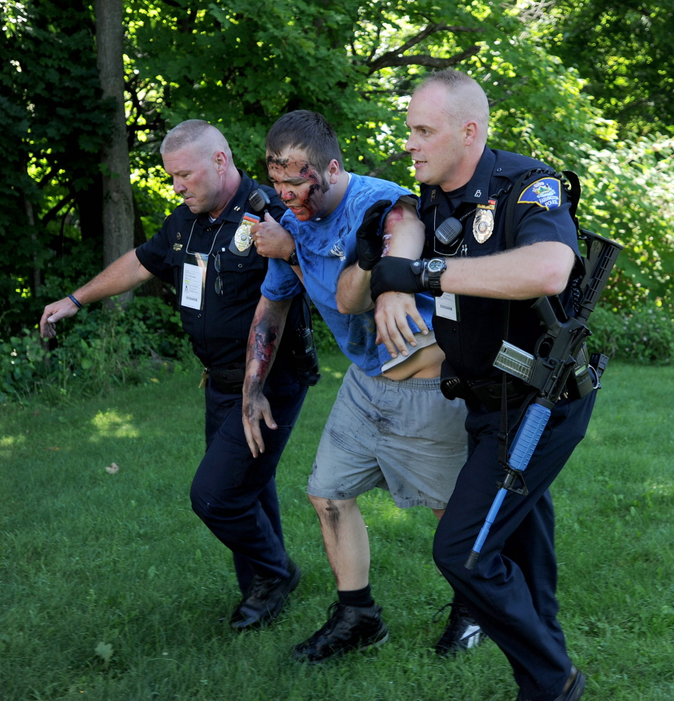 Farmington Police Chief Jack Peck, far left and officer Darin Gilbert, far right, help a person portraying a victim of a car bombing on Friday.