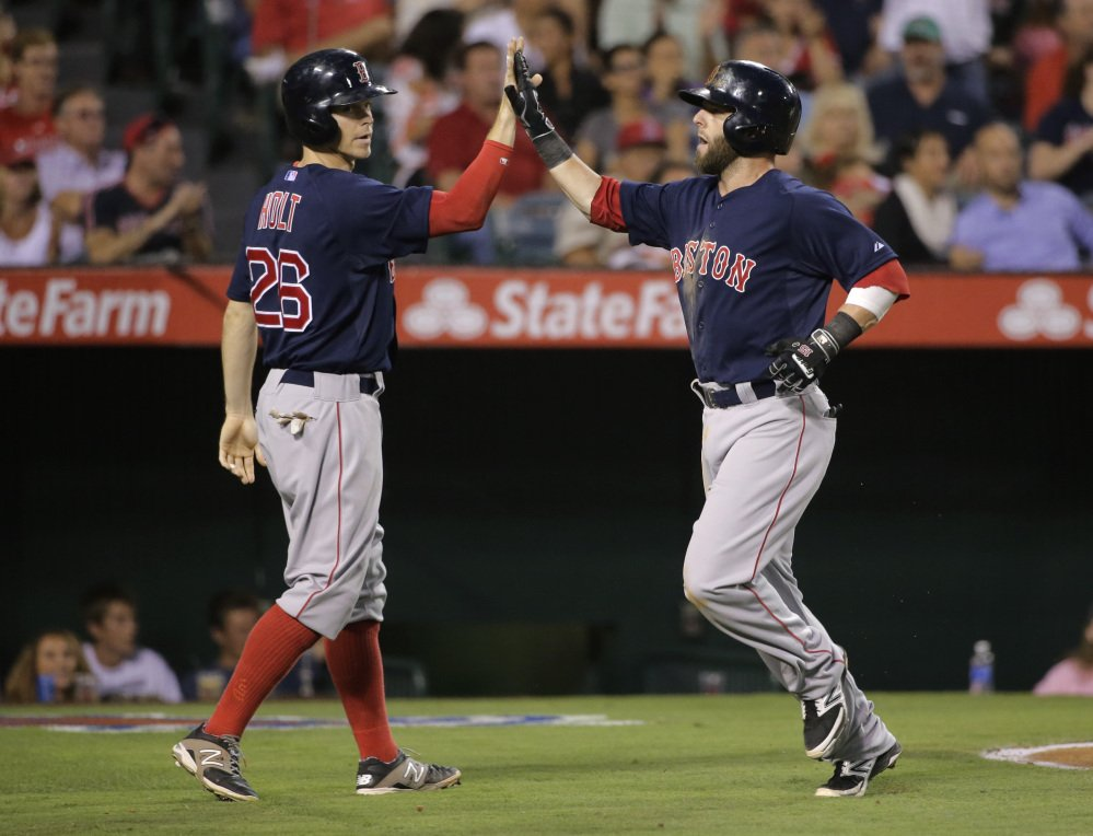 Boston's Brock Holt, left, and Dustin Pedroia celebrate after scoring on a double by Yoenis Cespedes in the third inning against the Los Angeles Angels on Friday in Anaheim, Calif.