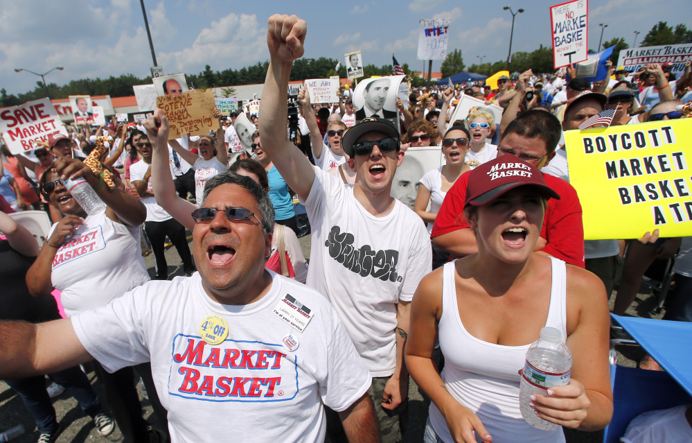 Market Basket employees from the Billerica, Mass., store cheer during a rally at Market Basket in Tewksbury, Mass., last week. Thousands of Market Basket supermarket employees and their supporters are calling for the reinstatement of their fired CEO.