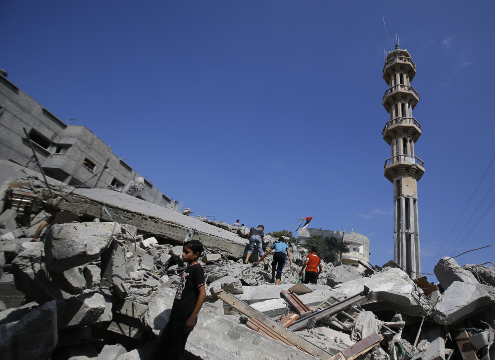 Palestinians stand in rubble of the al-Qassam mosque in Nuseirat refugee camp, central Gaza Strip, after it was hit by an Israeli airstrike, Saturday.