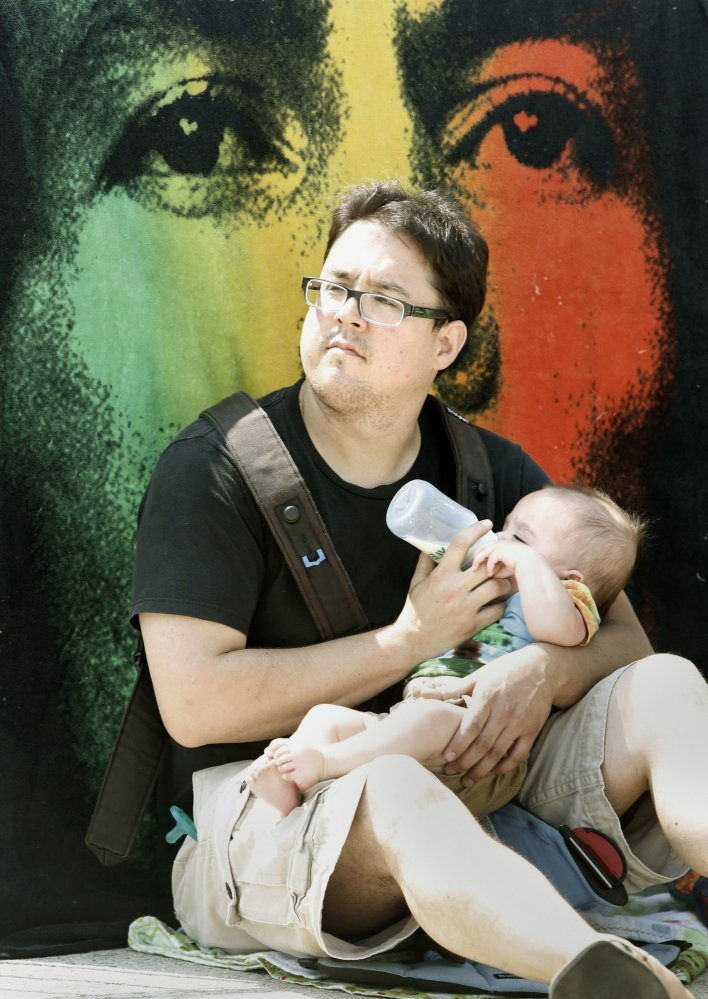 Tai Choo of Brunswick feeds his 5-month-old baby, Mateo, in front of a Bob Marley blanket.
