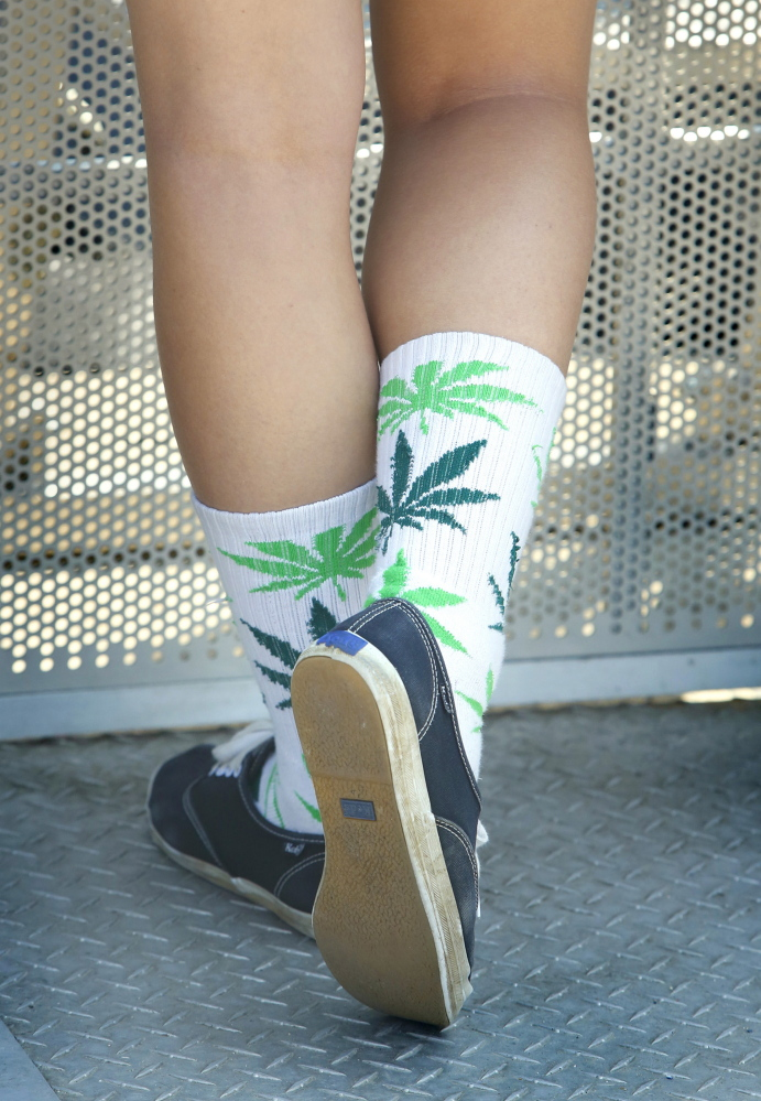 Sierra Prescott of Machias wears socks decorated with images of marijuana leaves while she listens to Soul Rebel Project.