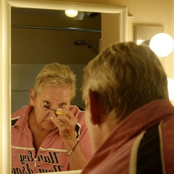 Pam Hillock of Hollis applies makeup at her home, which was difficult to do before she had a brain procedure to end physical shaking caused by essential tremor, a neurological disorder.