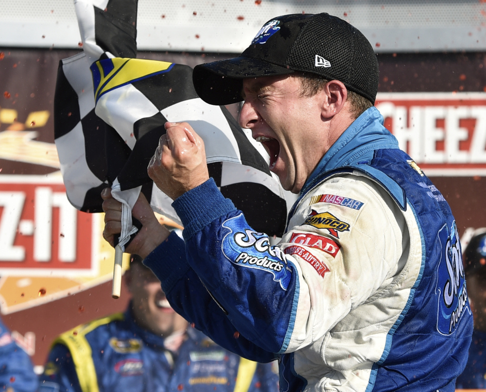 AJ Allmendinger waves the checkered flag as he celebrates Sunday in Victory Lane after winning the NASCAR Sprint Cup Series race at Watkins Glen International.