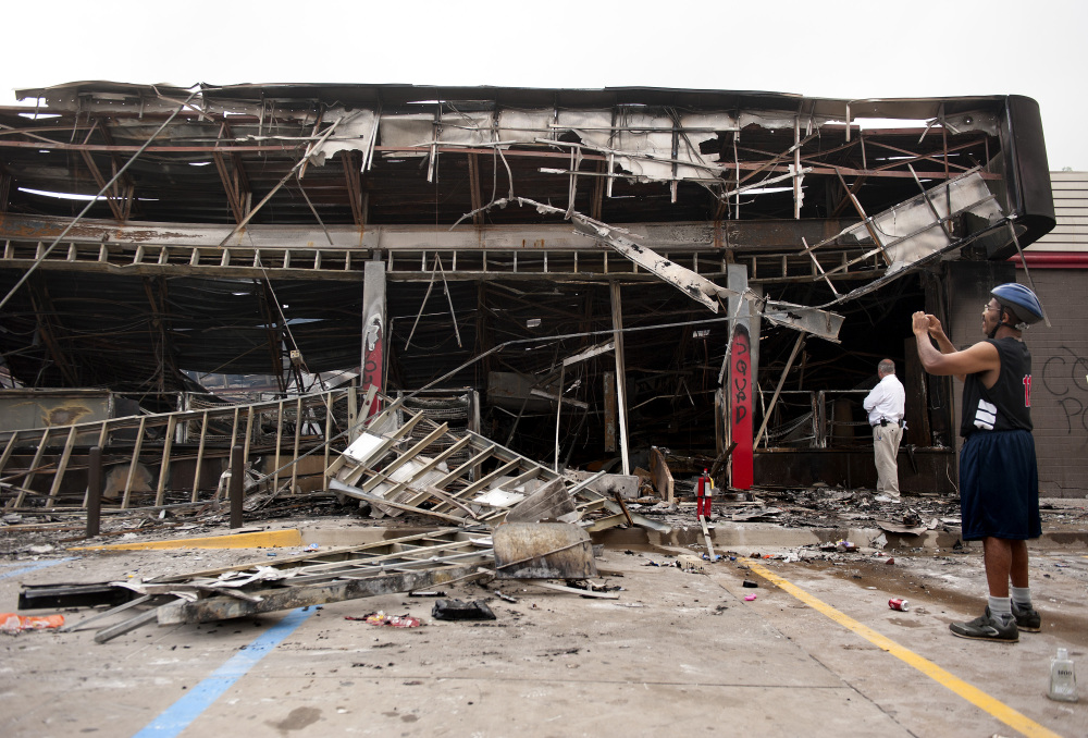 Passers-by and media take a closer look Monday, at the burned-out shell of the QuikTrip gas station torched during the violence that erupted in Ferguson, Mo. overnight following a candle-light memorial for 18-year-old shooting victim Michael Brown.