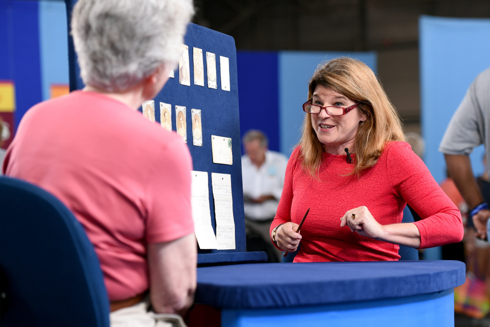 """This Aug. 9, 2014 photo released by Antiques Roadshow shows Leila Dunbar appraising a collection of early Boston baseball memorabilia for the program """"Antiques Roadshow"""" in New York."""