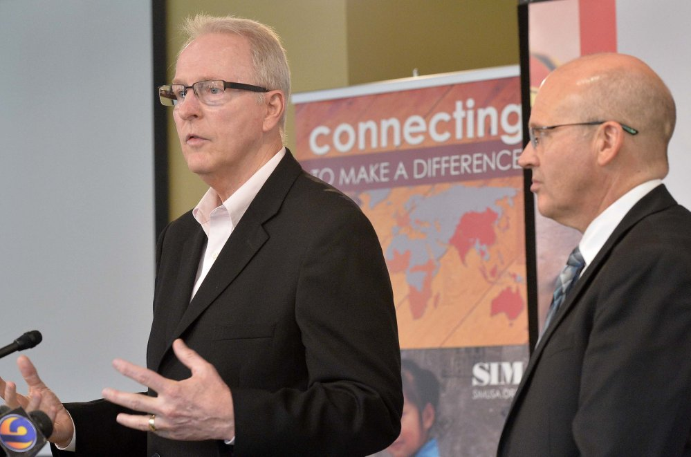 SIM USA President Bruce Johnson, left, and Dr. Stephen Keener, director of the Mecklenburg County Health Department, speak during a news conference Monday at SIM USA headquarters in Charlotte, N.C.