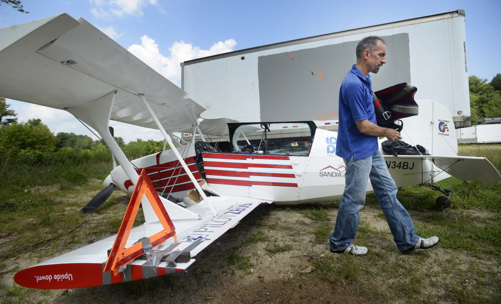 """Billy Werth removes belongings from his single-engine experimental aircraft Monday at Copp Motors in Cumberland, where the wreckage was towed after he crash-landed Sunday in Standish. """"I'm just happy to be here,"""" said Werth, whose injuries were minor."""