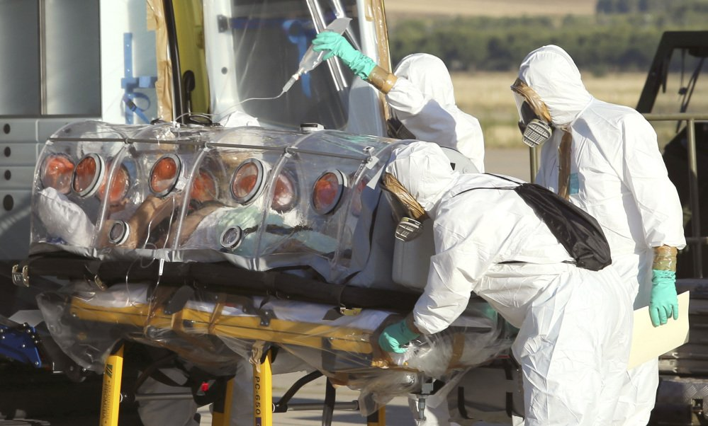 Aid workers and doctors transfer Miguel Pajares, a Spanish priest who was infected with the Ebola virus while working in Liberia, from a plane to an ambulance as he leaves the Torrejon de Ardoz military airbase, near Madrid, Spain.