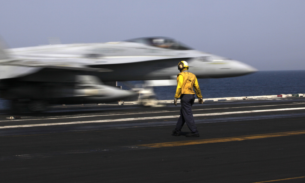A U.S. F/A-18 fighter jet takes off for Iraq from the flight deck of the aircraft carrier USS George H.W. Bush on Monday. U.S. military officials say American aircraft struck and destroyed several vehicles Sunday that were part of an Islamic State group convoy moving to attack Kurdish forces defending the northeastern Iraqi city of Irbil.