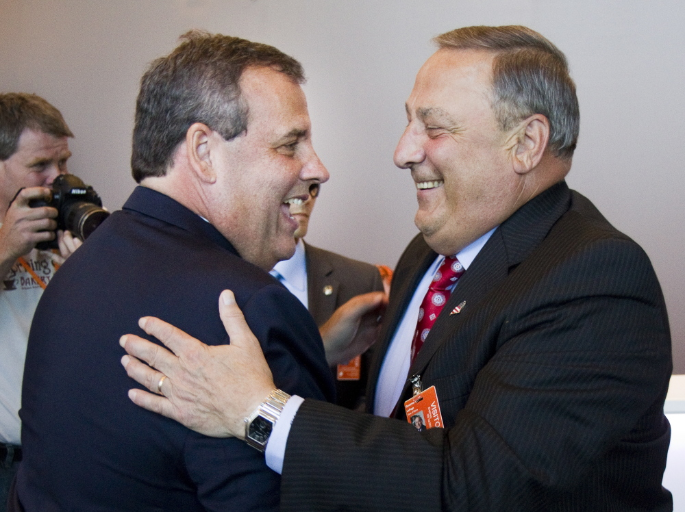 New Jersey Gov. Chris Christie and Maine Gov. Paul LePage greet one another before a tour of C&L Aviation in Bangor on Tuesday.